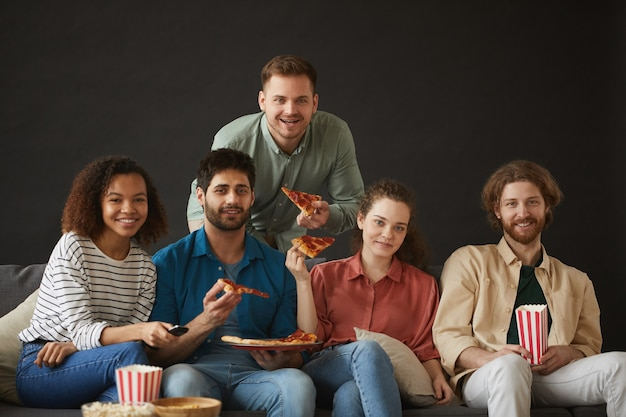 Большая группа друзей ест пиццу и закуски, наслаждаясь вечеринкой дома, сидя на большом диване