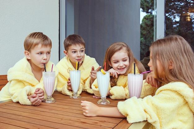 우유 칵테일과 함께 좋은 시간을 보내는 친구의 큰 그룹.