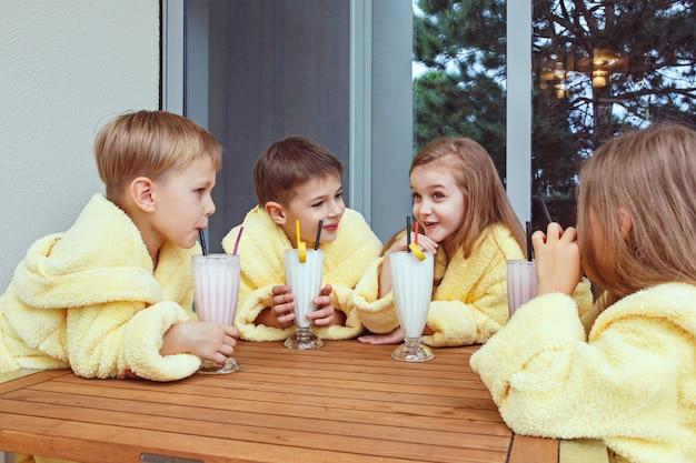 ミルクカクテルでグーグタイムを取っている友人の大規模なグループ。黄色いテリーのガウンで幸せな笑顔の男の子と女の子。キッズファッションコンセプト