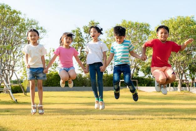 都市公園でのカジュアルな服で晴れた日の間に遊んで、一緒にジャンプ手を繋いでいる幸せなアジア笑顔幼稚園の子供の友人の大規模なグループ。