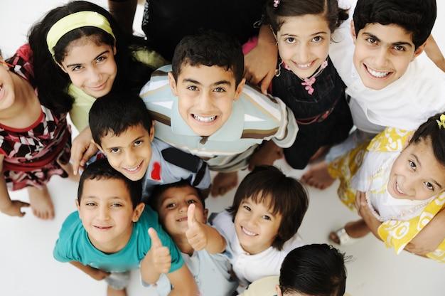 Большая группа счастливых детей, разных возрастов и рас, толпа