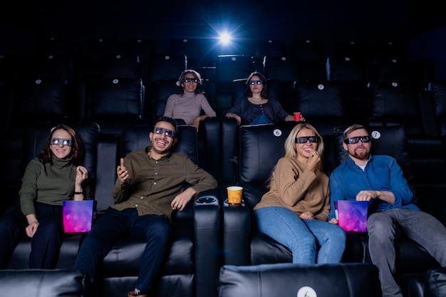 映画館で余暇を過ごし、面白いアクション映画を見ている3d眼鏡の幸せな若い友人の大規模なグループ