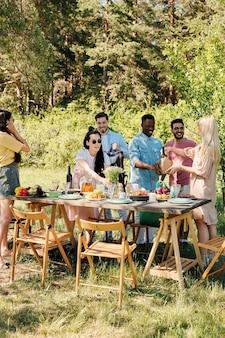 屋外ディナーのテーブルを提供しながら、スーパーマーケットから食品の袋を開梱する幸せな若い異文化間の友人の大規模なグループ