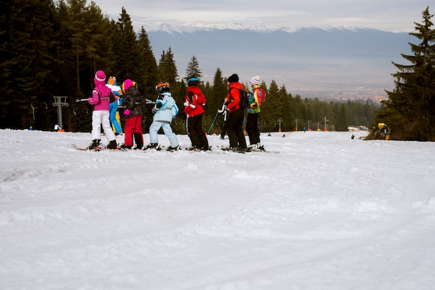 행에 서서 눈 산에서 스키를 배우는 유아의 큰 그룹.