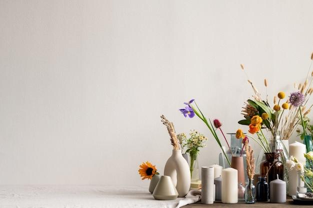 Большая группа различных творческих керамических, глиняных и стеклянных ваз ручной работы с засушенными и живыми цветами и ароматическими свечами на столе у стены