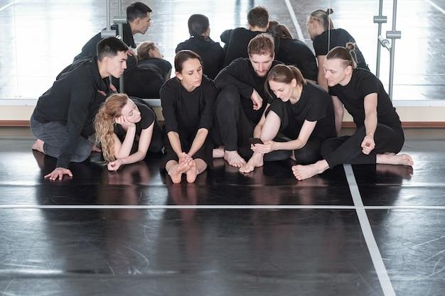 Большая группа молодых студентов курса современных балетных танцев сидит на полу у зеркала, пока одна из девушек прокручивает в смартфоне