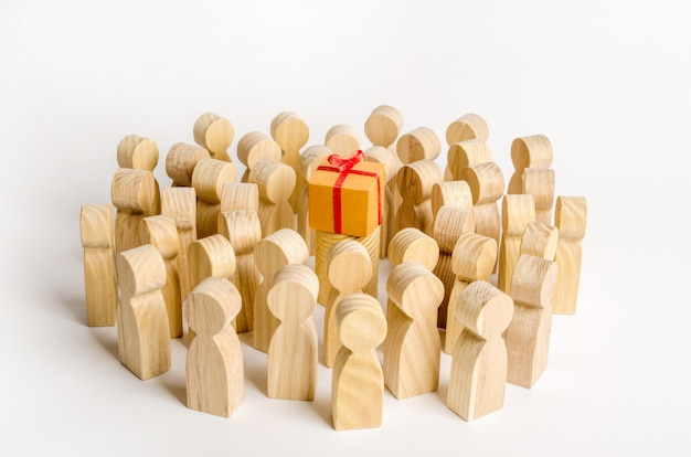 A large group of people surrounds a box with a present.