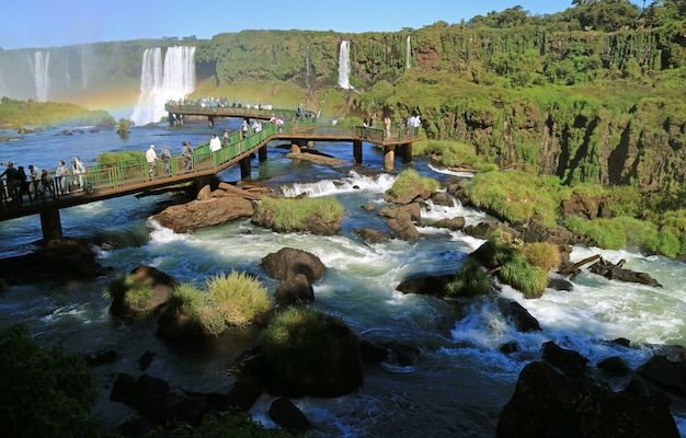 Large group of visitor on the boardwalk amongst the powerful stream, iguazu falls at brazilian side, brazil