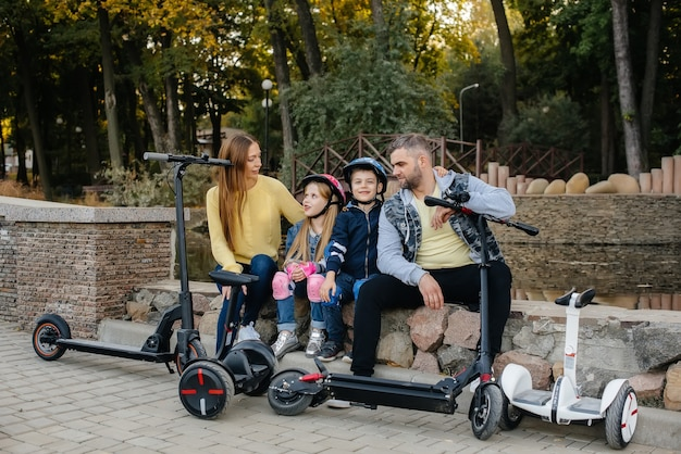 A large happy family rides segways and electric scooters in the park on a warm autumn day during sunset