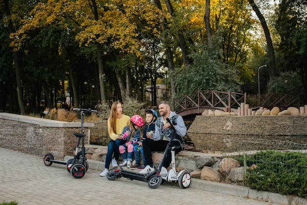 A large happy family rides segways and electric scooters in the park on a warm autumn day during sunset.