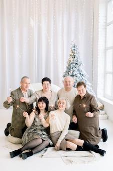 폭죽이 크리스마스 트리 앞에 앉아 큰 행복한 가족