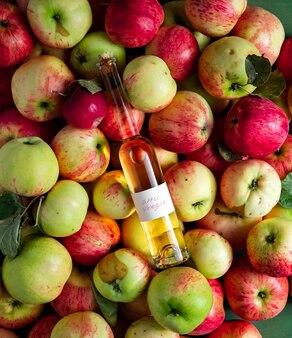 Large heap of ripe apples, bottle of homemade apple vinegar on top