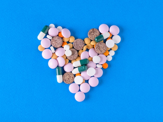 A large heart of colorful pills on blue background.