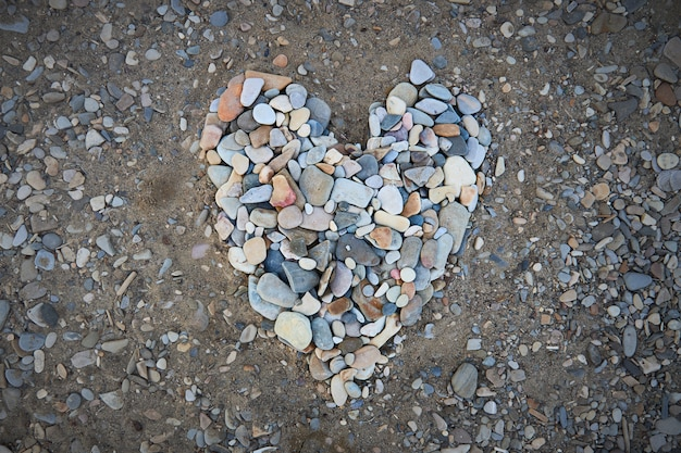 A large heart made of small pebbles on the seashore