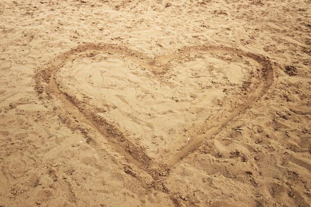 Большая форма сердца, нарисованная в песке морского пляжа для символического туристического отдыха или концептуальных проектов