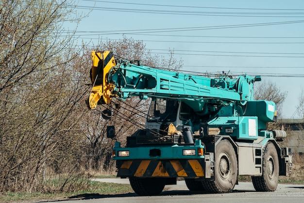 クレーンの付いた大型の重い車が、電線の下を道路に沿って走行しています。