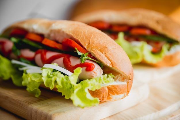 Большой хот-дог с овощами на столе.