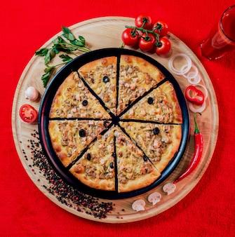 黒いプレートに大きな温かいピザ。