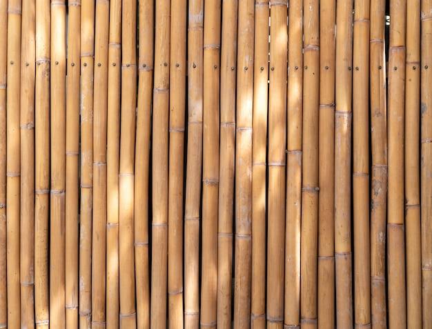 黄色の竹の棒の壁、竹の柵のテクスチャ背景、抽象的な背景の自然光スポットの大きな画像