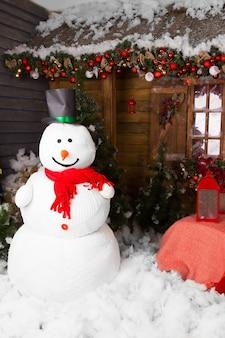 면 눈으로 바닥에 서 있는 아름다운 크리스마스 장식으로 둘러싸인 모자를 쓴 대형 실내 겨울 눈사람.