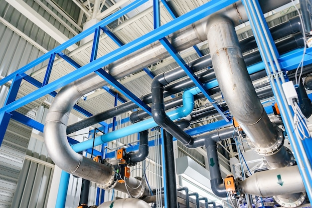 Large industrial water treatment and boiler room. shiny steel metal pipes and blue pumps