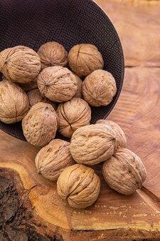 暗いカップから木製のテーブルに注がれた大きな殻付きクルミナッツ