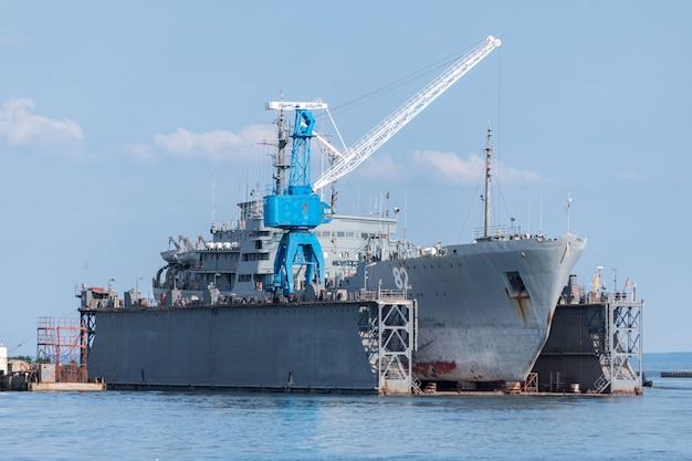 수리를 위해 조선소에서 대형 철 해군 선박. 조선소에서 큰 크레인입니다. 푸른 바다 항구