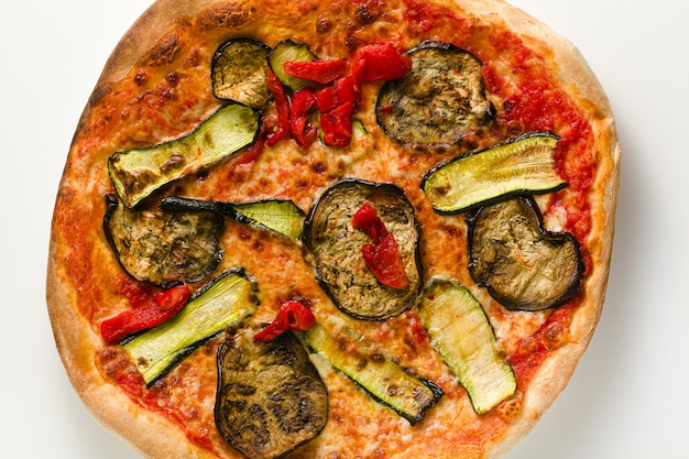 白いテーブルに分離された野菜のグリルと大きなイタリアのピザ