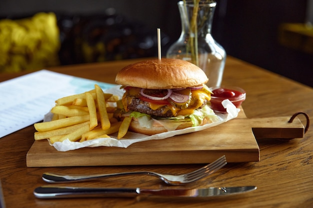 Большой сочный гамбургер с картофелем фри на деревянной доске