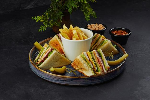 チーズとハムの大きなジューシーなサンドイッチがフライドポテトのプレートにあります