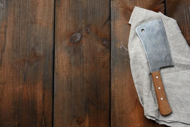 茶色の木のテーブルで肉や野菜を切るための大きな包丁