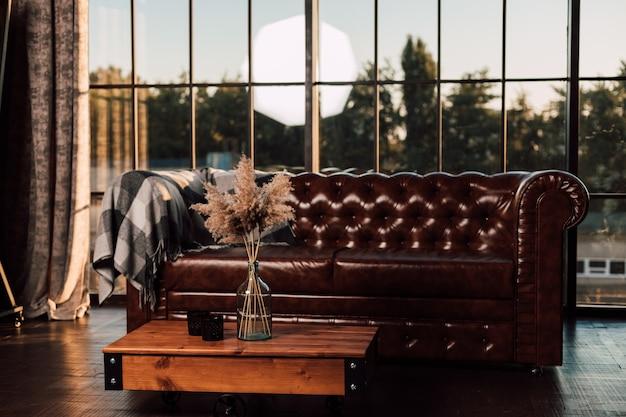Большой кожаный диван на фоне большого окна в современном интерьере