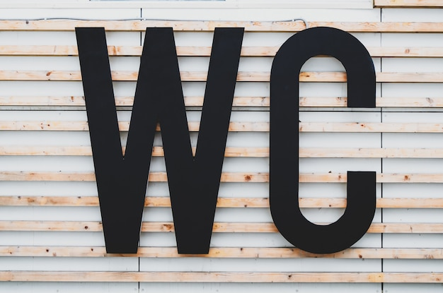 Large letters wc on facade of building with wood paneling. public toilet sign in a city park. international restroom symbol. outdoor wc, washroom.