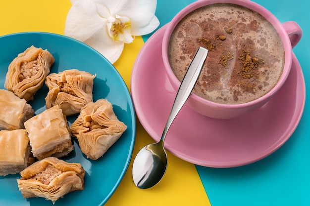 A large lilac cup of coffee with cinnamon, baklava and a white orchid flower on a bright surface.
