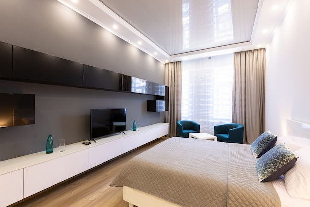 현대적인 스타일의 침대, 가구 및 tv가있는 넓은 거실