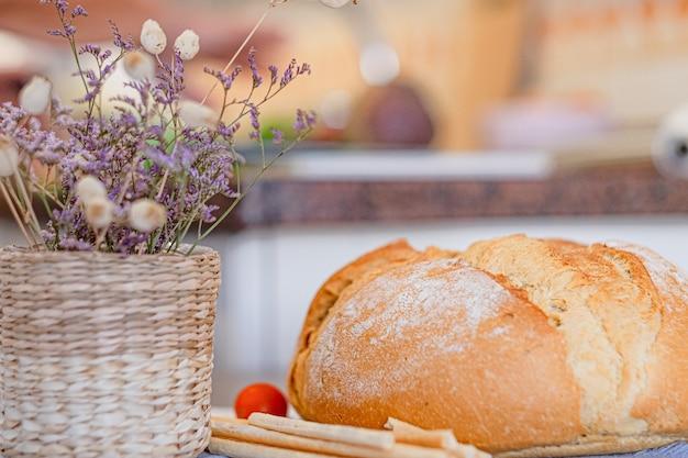 ホームテーブルの上の大きなパン。ブレッドスティック、ドライフラワーのバスケット