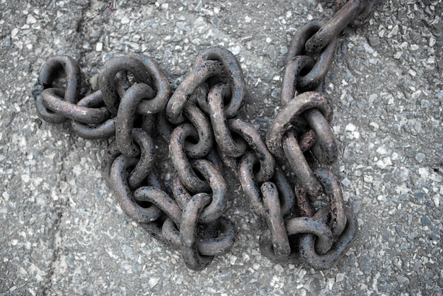 A large long chain against the backdrop of the sidewalk closeup