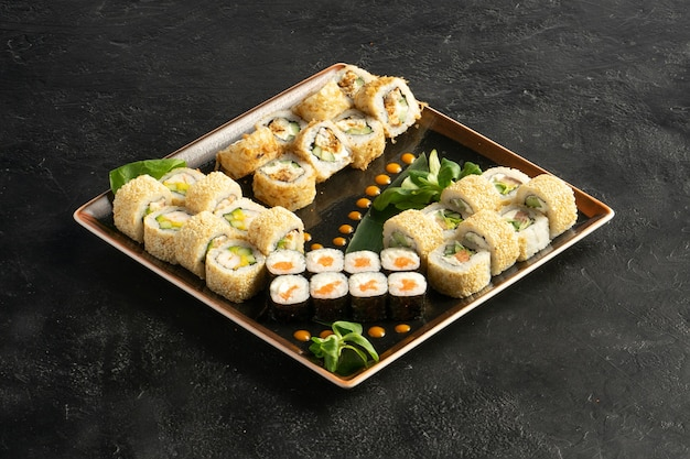 Large maki sushi set with a varied assortment of japanese rolls in a square plate on a black stone table