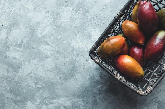 Большие манго в плетеной корзине на сером фоне. здоровая еда, веган