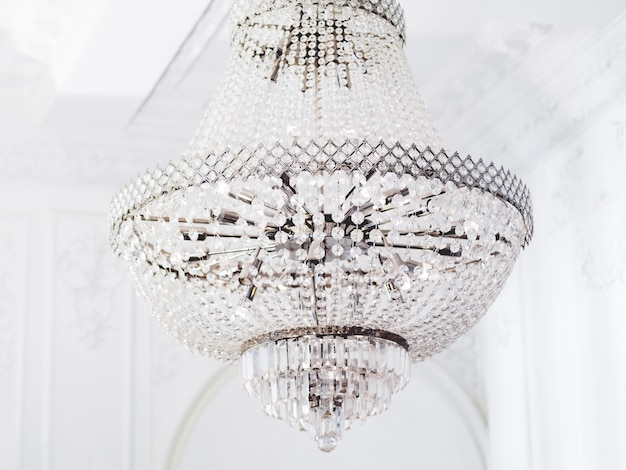 Large many-tier chandelier with glass pendants. interior element with crystal details in white room.