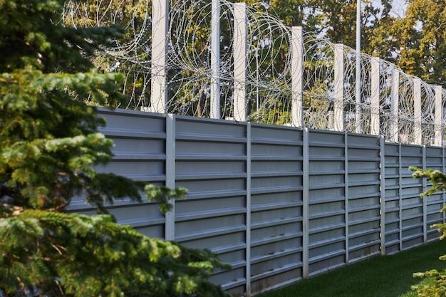 有刺鉄線で囲まれた大きな金属フェンス