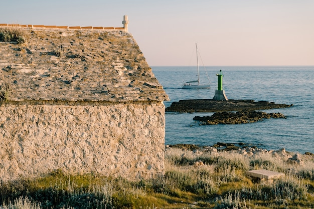 A large metal green lighthouse on a rock in the sea near cape punta planka in croatia