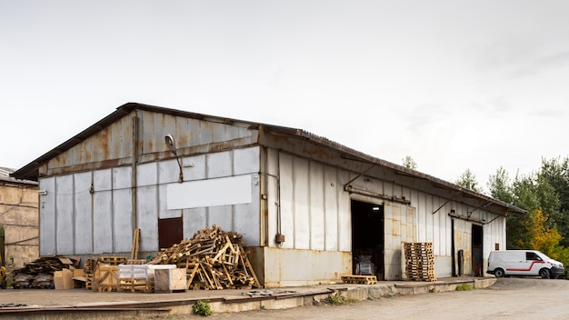 A large metal industrial warehouse for storing goods, next to it are wooden pallets for storing goods