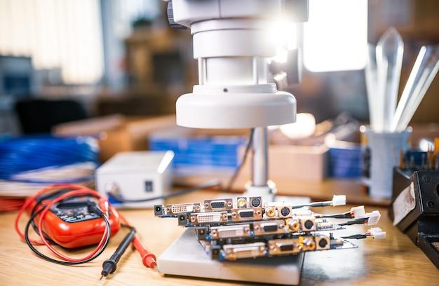 과학 실험실에서 전자 부품 연구를 준비하기 위해 대형 현대 전자 현미경과 임베디드 마이크로 회로가 테스트 플레이트에 쌓입니다.