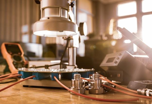 대형 현대 전자 현미경. 작업장 테이블의 마이크로파 동축 커넥터 및 전자 디지털 멀티 미터. 과학 실험실에서 고주파 무선 전자 부품 연구