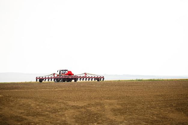 곡물 파종을 위해 겨울 후 밭을 준비하기위한 대형 현대 트랙터