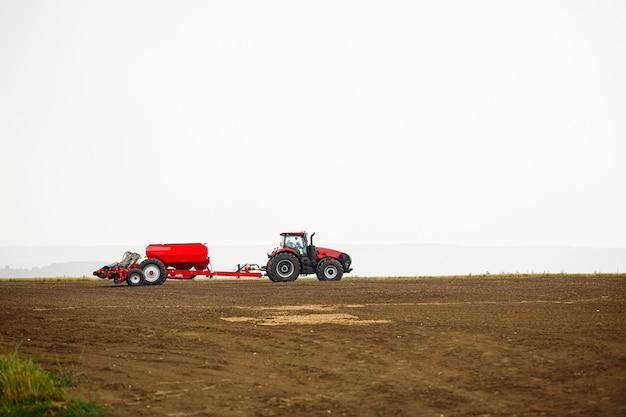 冬の後に穀物を播種するためのフィールドを準備するための大型の近代的なトラクター