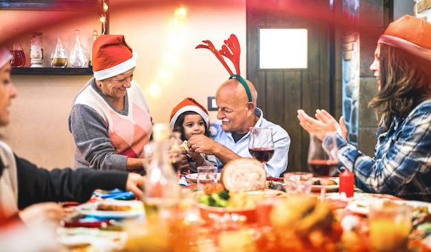 Large multi generation family having fun at christmas supper party - winter holiday x mas concept with parents and children eating together opening gifts at home - focus on grandpa and daugther hands