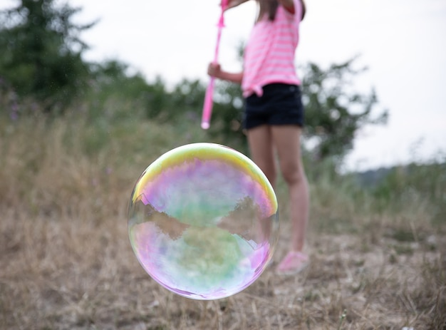 Large multicolored soap bubble on a blurred background.
