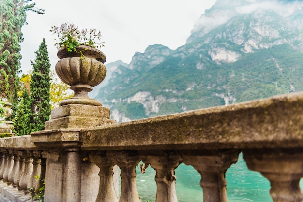 Large natural stone vases decorate the balustrade of a lakeside promenade